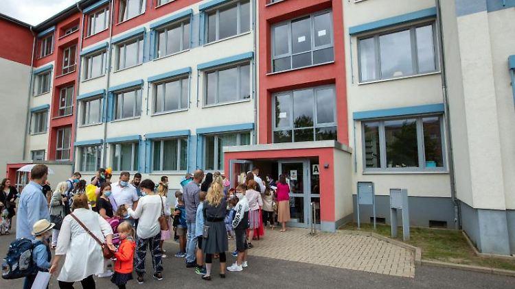 Schulanfänger und ihre Eltern warten auf Corona-Kontrollen und gehen zur Einschulungsfeier. Foto: Jens Büttner/dpa-Zentralbild/dpa