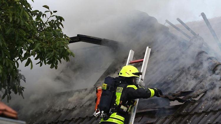 Ein Feuerwehrmann hebt Ziegel von einem brennenden Dachstuhl. Foto: Marc Webersinn/5vision.media/dpa
