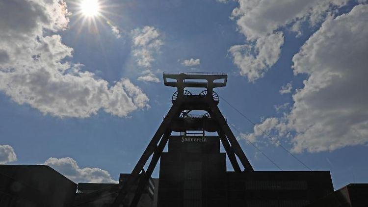 Die Sonne scheint hinter dem Förderturm der Zeche Zollverein. Foto: Oliver Berg/dpa/Archivbild
