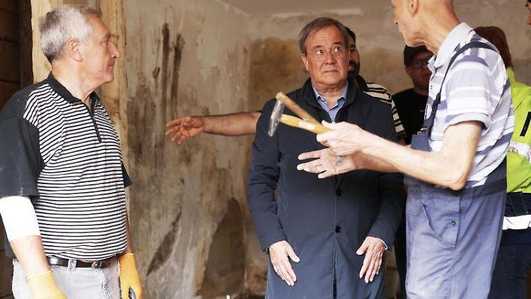Ministerpräsident Armin Laschet mit Anwohnern in einem zerstörten Haus. Foto: Oliver Berg/dpa