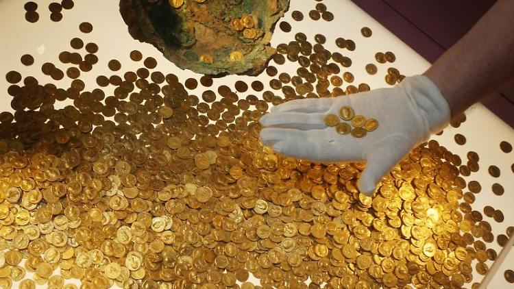 Römische Goldmünzen des Trierer Goldschatzes werden im Rheinischen Landesmuseum Trier platziert. Foto: Thomas Frey/dpa/Archivbild