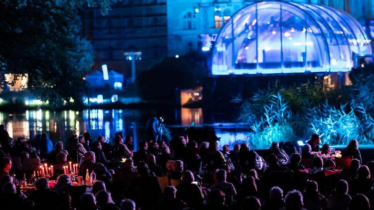 Menschen verfolgen 2018 im Maschpark in Hannover die Open Air Aufführung der Oper Don Giovanni. Foto: Peter Steffen/dpa/Archivbild