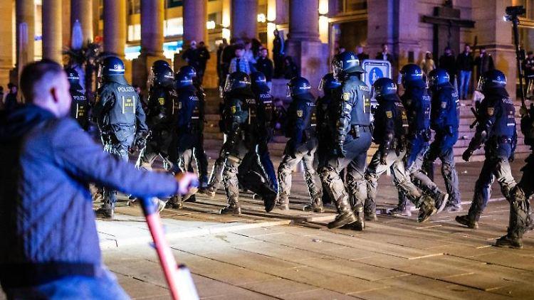 Einsatzkräfte der Polizei laufen über den Schlossplatz. Foto: Christoph Schmidt/dpa/archivbild
