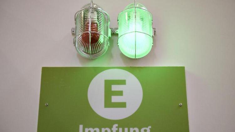 Eine grüne Lampe leuchtet am Eingang eines Corona-Impfzentrums. Foto: Christopher Neundorf/dpa/Symbolbild