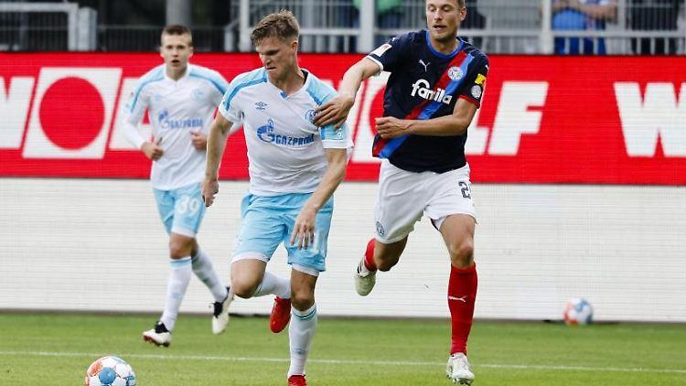 Schalkes Marius Bülter (M) setzt sich im Zweikampf gegen Kiels Hauke Wahl (r) durch. Foto: Frank Molter/dpa/Archivbild