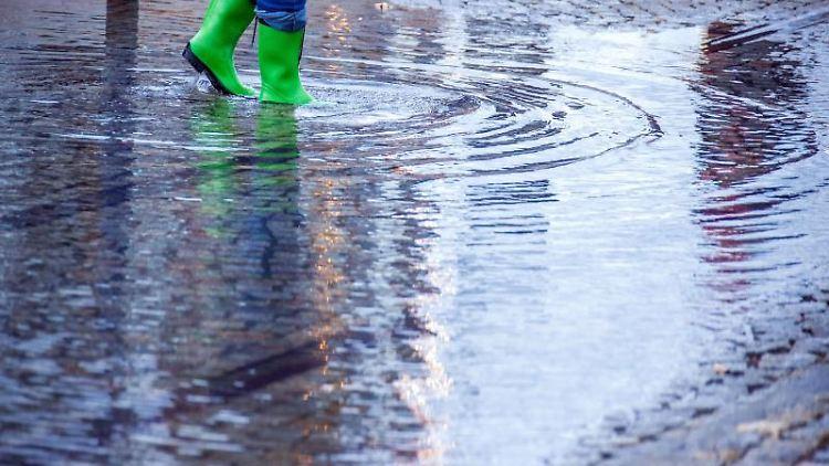 Mit Gummistiefeln geht eine Frau über eine leicht überflutete Straße. Foto: Jens Büttner/dpa-Zentralbild/dpa/Symbolbild