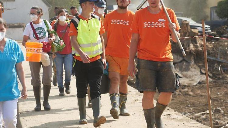 Freiwillige Helfer sind auf dem Weg zu den Haushalten, in denen sie bei den Aufräumungsarbeiten nach der Flut helfen. Foto: Thomas Frey/dpa