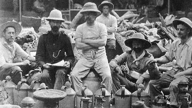 Britische Soldaten mit Raubkunst in Benin, 1897. Die Benin-Expedition von 1897 war eine Strafexpedition einer britischen Streitmacht unter Admiral Sir Harry Rawson. Während der Eroberung und Verbrennung der Stadt wurde ein Großteil der Kunst des Landes, einschließlich der Benin-Bronzen, entweder zerstört, geplündert oder zerstreut.