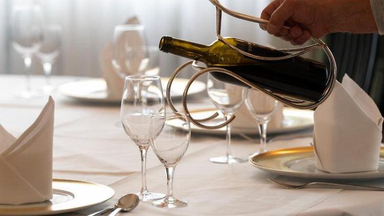 Ein Mitarbeiter eines Restaurants schenkt an einem gedeckten Tisch Wein ein. Foto: Bernd Weißbrod/dpa/Archivbild