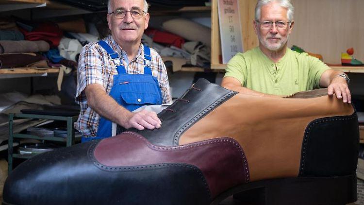 Die Schuhmachermeister Matthäus Jörg (l) und Johannes Schunk stehen hinter einem überdimensionierten Schuh. Foto: Marijan Murat/dpa