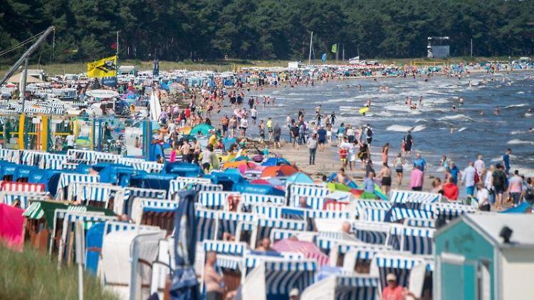 Menschen bevölkern den Ostseestrand. Foto: Stefan Sauer/dpa