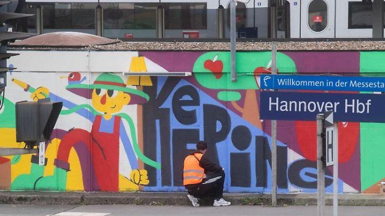 Das Künstlerkollektiv DOTU sprayt ein großes Kunstwerk auf ein Gebäude der Deutschen Bahn auf Gleis 9 und 10 des Hauptbahnhofes in Hannover. Foto: Julian Stratenschulte/dpa