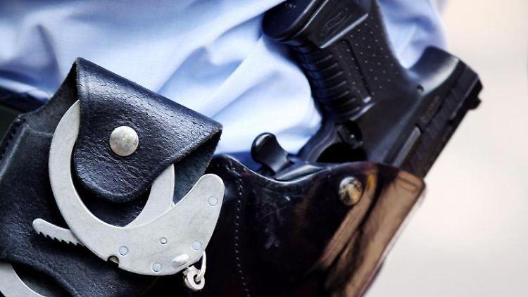 Ein Polizist mit Handschellen und Pistole am Gürtel. Foto: Oliver Berg/dpa/Symbolbild