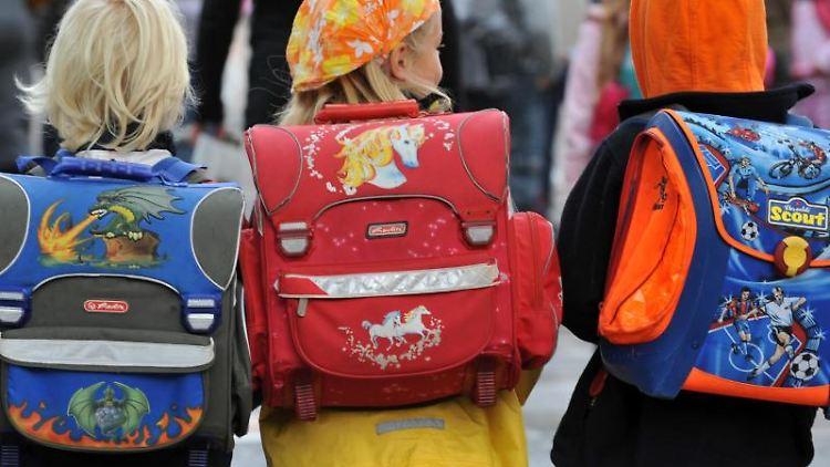 Drei Kinder laufen mit ihren Schulranzen zur Schule. Foto: dpa/Symbolbild