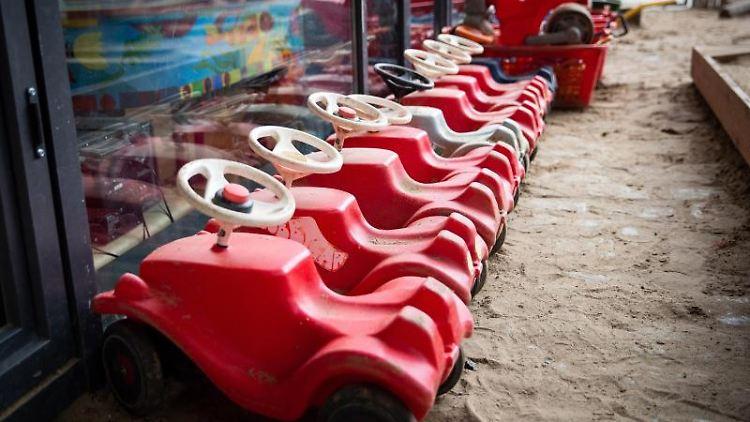 Mehrere Bobbycars stehen auf dem Spielplatz einer Kita. Foto: Christian Charisius/dpa/Symbolbild