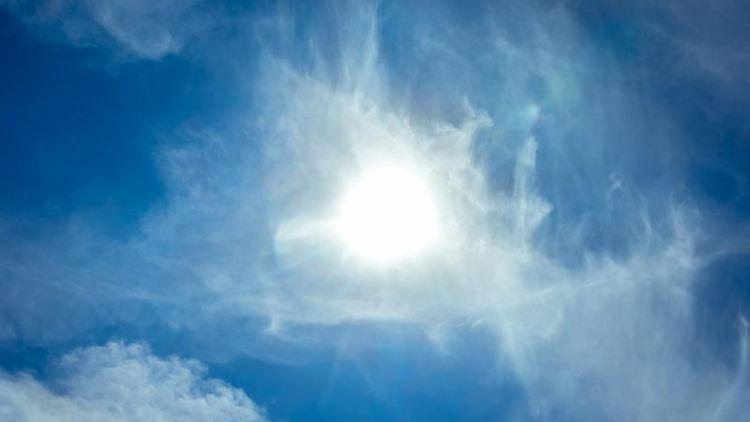 Die Sonne scheint durch leichte Zirrus-Wolken hindurch. Foto: Markus Scholz/dpa/Symbolbild