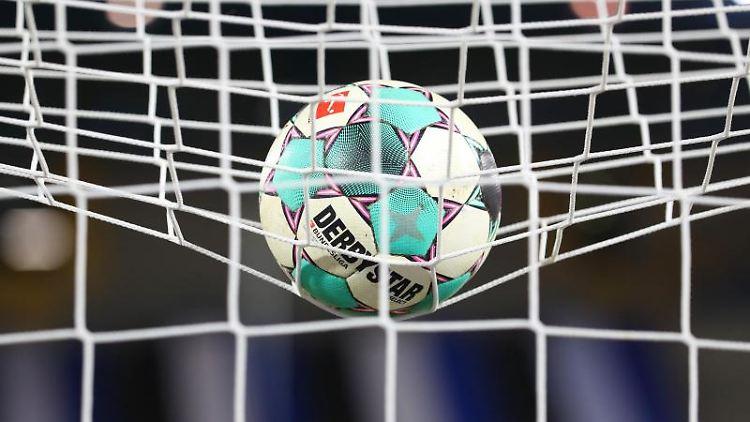 Ein Fußball liegt vor der Partie im Netz. Foto: Friso Gentsch/dpa/Symbolbild