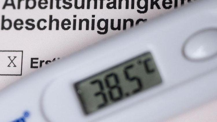 Ein Fieberthermometer liegt auf einer Arbeitsunfähigkeitsbescheinigung. Foto: Marijan Murat/dpa/Symbolbild