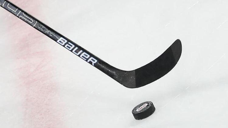 Ein Puck liegt vor einem Eishockey-Schläger auf dem Eis. Foto: Daniel Karmann/dpa/Symbolbild