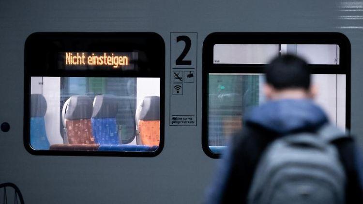 Ein Mann steht vor einem Zug, auf dem