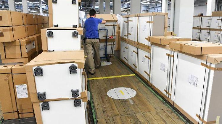 Ein Mitarbeiter des Küchenbauers Neue Alno GmbH transportiert im Lager Küchenmodule auf einer Sackkarre. Foto: Felix Kästle/dpa/Archivbild