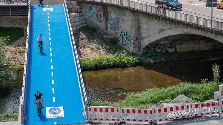 Menschen fahren mit ihren Fahrrädern über eine beheizbare Radbrücke. Foto: Christoph Schmidt/dpa/Archivbild