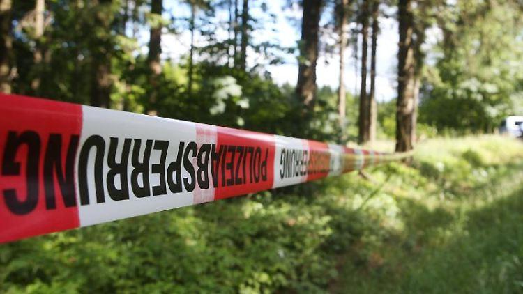 Ein Absperrband der Polizei ist in einem Waldstück angebracht. Foto: Bodo Schackow/ZB/dpa/Symbolbild