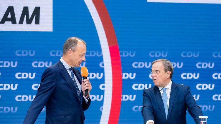 Friedrich Merz (l) spricht neben Armin Laschet. Foto: Christoph Soeder/dpa/Archivbild
