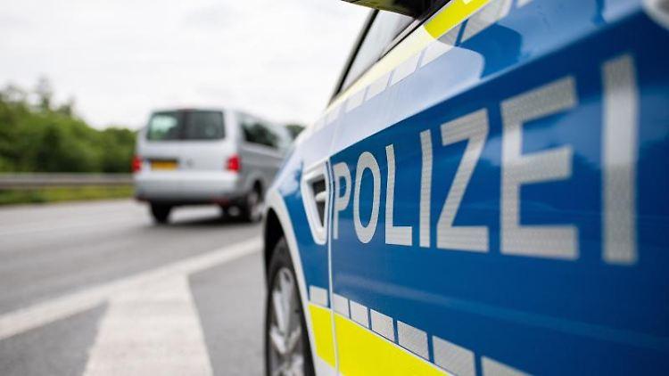 Ein Streifenwagen der Polizei steht auf einer Straße. Foto: Guido Kirchner/dpa/Symbolbild