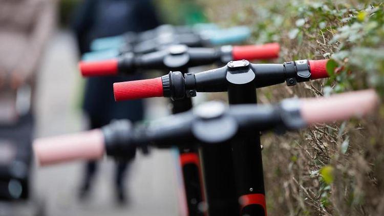 Einige E-Scooter stehen auf einem Gehweg neben einer Hecke. Foto: Rolf Vennenbernd/dpa/Archivbild
