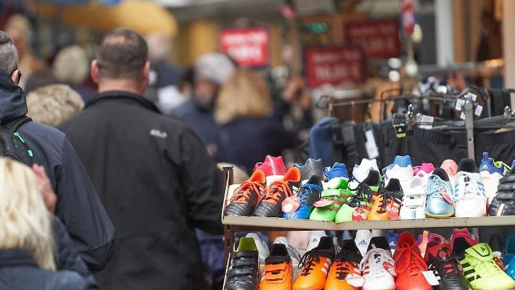 Fußgänger gehen durch die Stadt an geöffneten Läden vorbei. Foto: Thomas Frey/dpa/Symbolbild