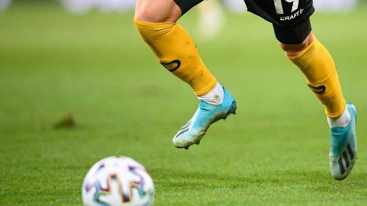 EinFußballspieler spielt denBall. Foto: Robert Michael/dpa-Zentralbild/dpa/Symbolbild