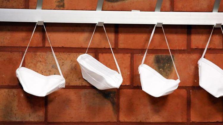Mund-Nase-Schutzmasken hängen an Haken. Foto: Rene Traut/dpa/Symbolbild