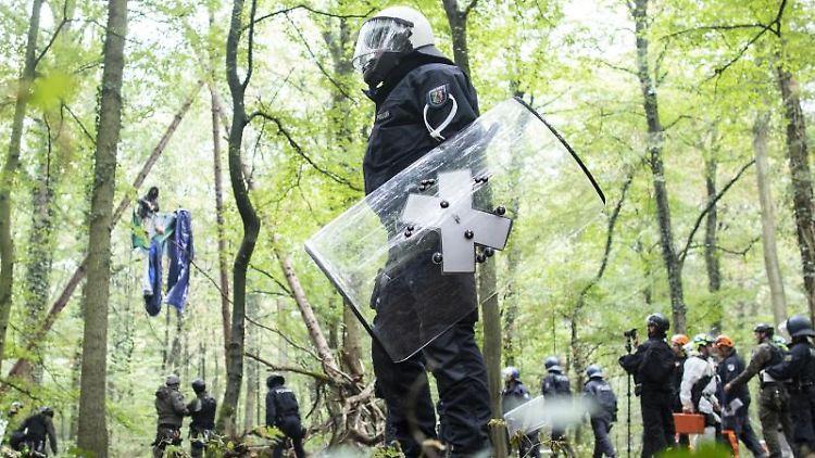 Polizisten stehen vor einer Barrikade, in der sich eine Aktivistin festgebunden hat. Foto: Marcel Kusch/dpa/Archivbild