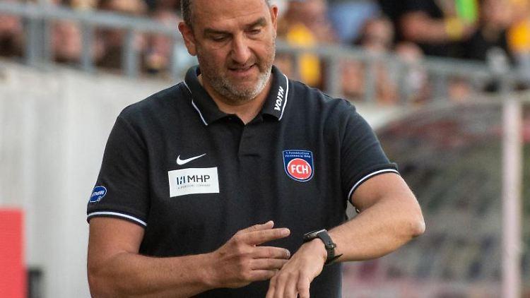 Heidenheims Trainer Frank Schmidt schaut auf seine Uhr. Foto: Stefan Puchner/dpa/archivbild