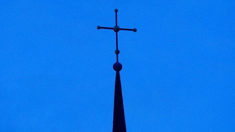 Das Kreuz einer Kirche ist in der Abenddämmerung zu sehen. Foto: Friso Gentsch/dpa/Symbolbild