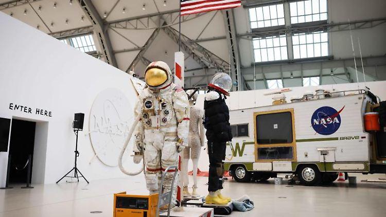 Ein Weltraumanzug und ein umgebautes Wohnmobil sind in