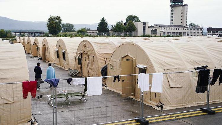 Aus Afghanistan evakuierte Menschen stehen auf der Ramstein Air Base zwischen Zelten. Foto: Uwe Anspach/dpa/archivbild