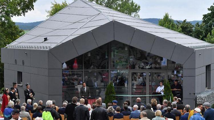 Besucher der Eröffnung stehen vor dem neuen Geoinformationszentrum Geopark Kyffhäuser an der Barbarossahöhle. Foto: Martin Schutt/dpa-Zentralbild/dpa