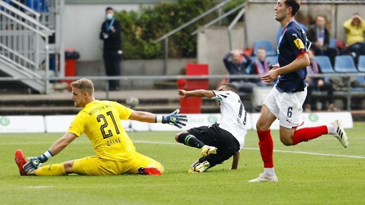 Hannovers Linton Maina (M) trifft gegen Kiels Torwart Thomas Dähne (l) und Marcel Benger zum 3:0. Foto: Frank Molter/dpa