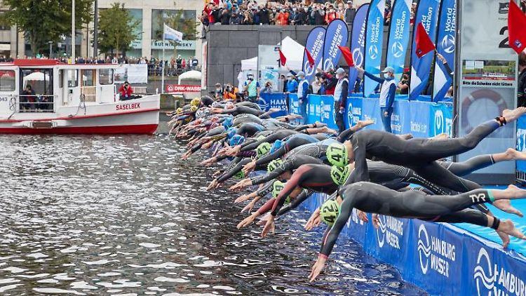 Teilnehmerinnen springen beim Start in die Binnenalster. Foto: Georg Wendt/dpa