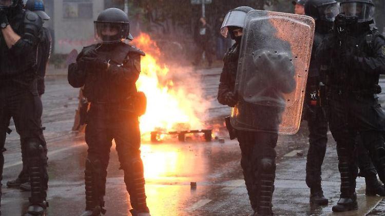 Polizisten stehen an einer brennenden Barrikade im Stadtteil Connewitz. Foto: Sebastian Willnow/dpa-Zentralbild/dpa