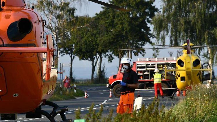 Einsatzkräfte stehen neben zwei Rettungshubschraubern auf einer Landstraße. Foto: Sebastian Klemm/Sebastian Klemm /dpa