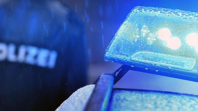 Ein Polizist steht vor einem Streifenwagen mit Blaulicht. Foto: Karl-Josef Hildenbrand/dpa/Symbolbild