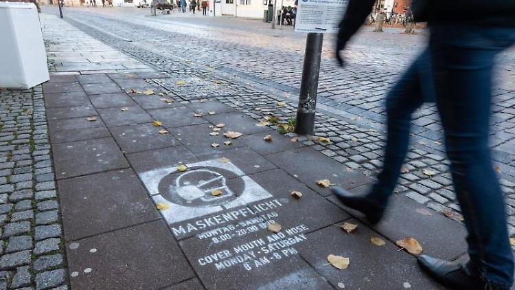 """""""Maskenpflicht"""" steht unter anderem auf einem Piktogramm, das auf den Gehweg gesprüht worden ist. Foto: Philipp Schulze/dpa/Symbolbild"""