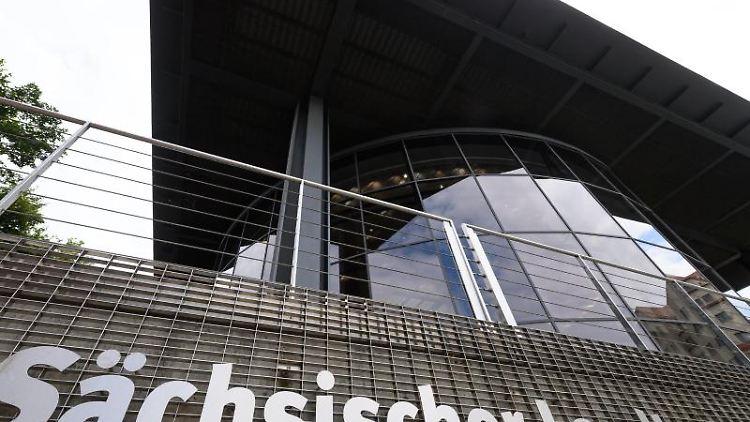 Sächsischer Landtag steht an einem Gitter am hintern Teil des Parlamentsgebäudes. Foto: Robert Michael/dpa-Zentralbild/dpa