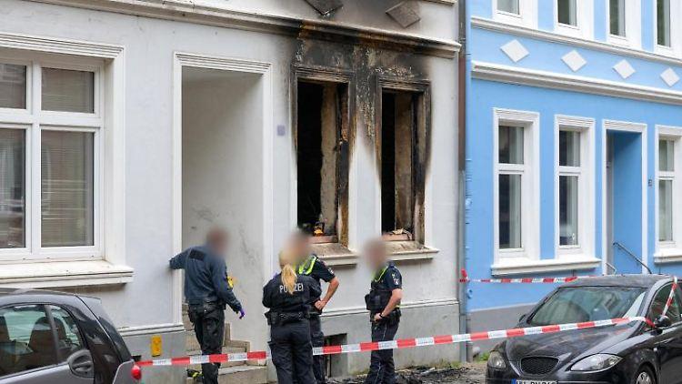 Zwei Brandermittler der Polizei stehen mit Polizisten vor der Brandwohnung. Foto: Jonas Walzberg/dpa/Archivbild