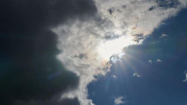 Die Sonne kommt hinter Wolken hervor. Foto: Annette Riedl/dpa/Symbolbild