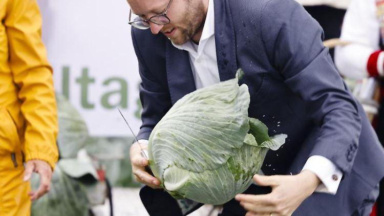 Agrarminister Jan Philipp Albrecht hält ein Messer und einen Kohlkopf in den Händen. Foto: Frank Molter/dpa