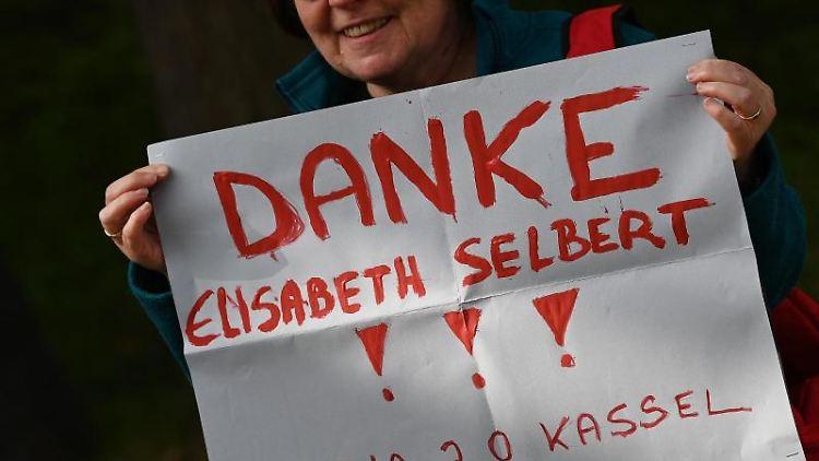 Eine Besucherin hält vor dem Festakt in der Hand. Foto: Swen Pförtner/dpa
